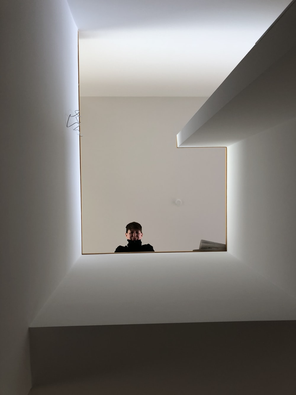 low-angle photography of man looking down from stair