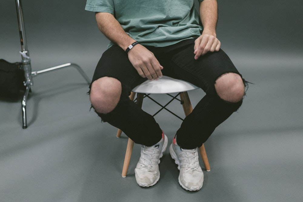 person sitting on white wooden stool