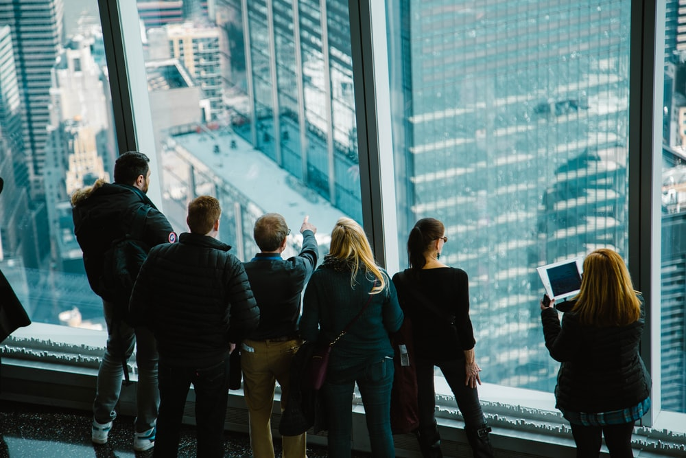 group of people in building looking outside