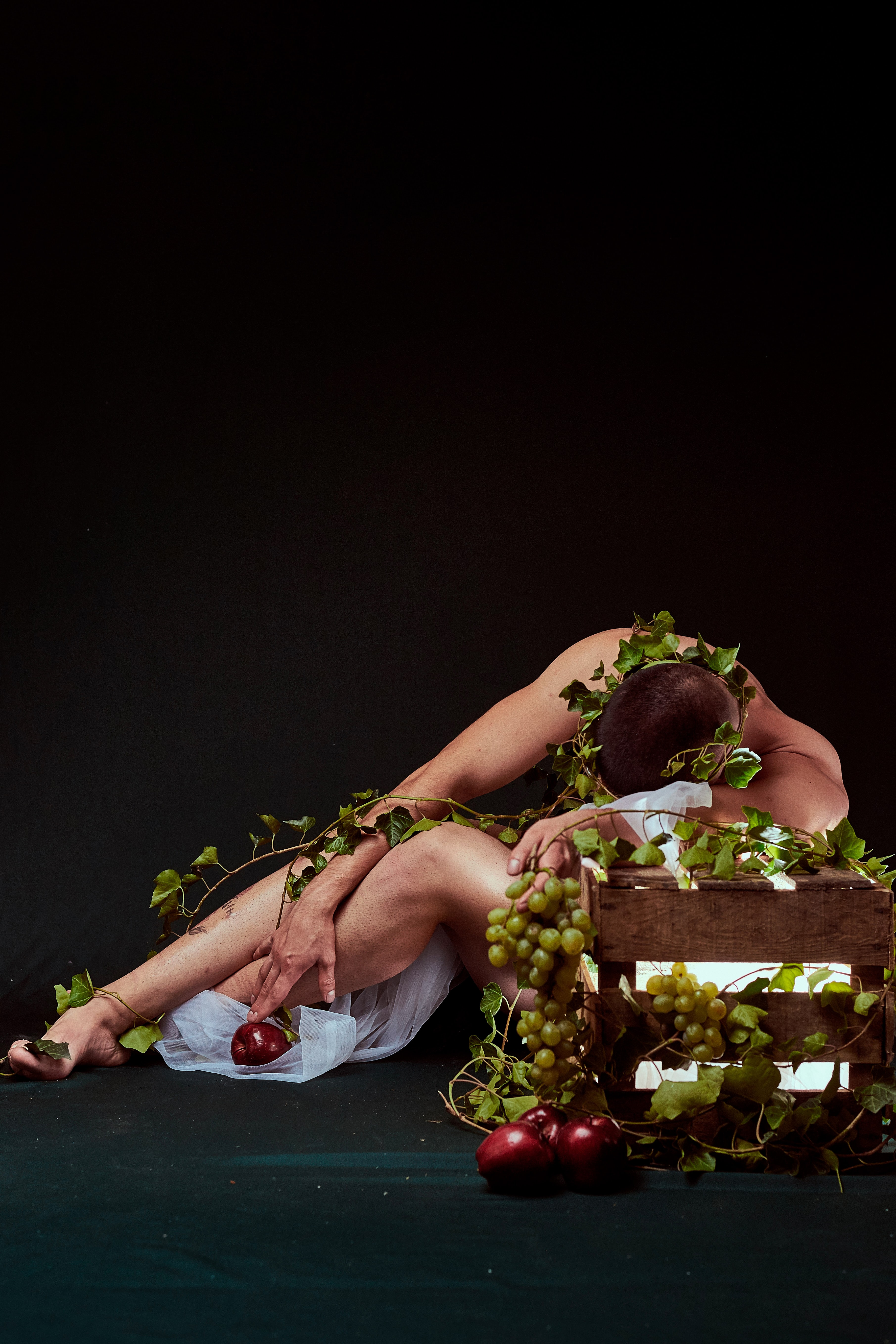 person laying down against brown box with grapes covering him