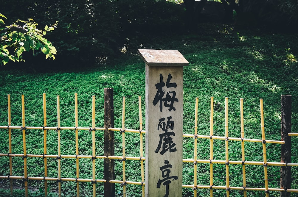 kanji text on wooden wall sign near fence
