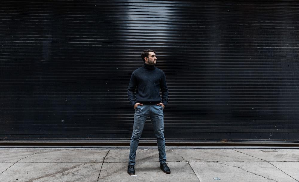 man standing near black shutter door
