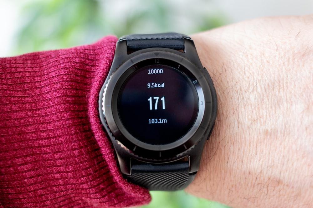 person wearing round black smartwatch
