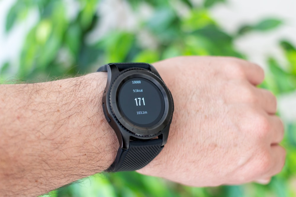 person showing of round black watch