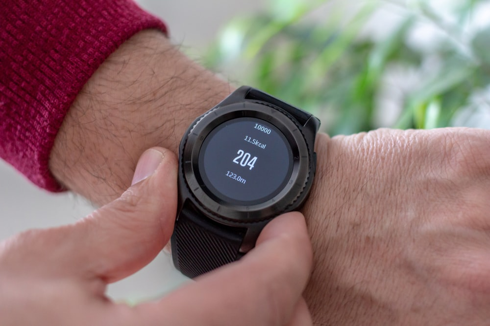 person wearing round black smartwatch