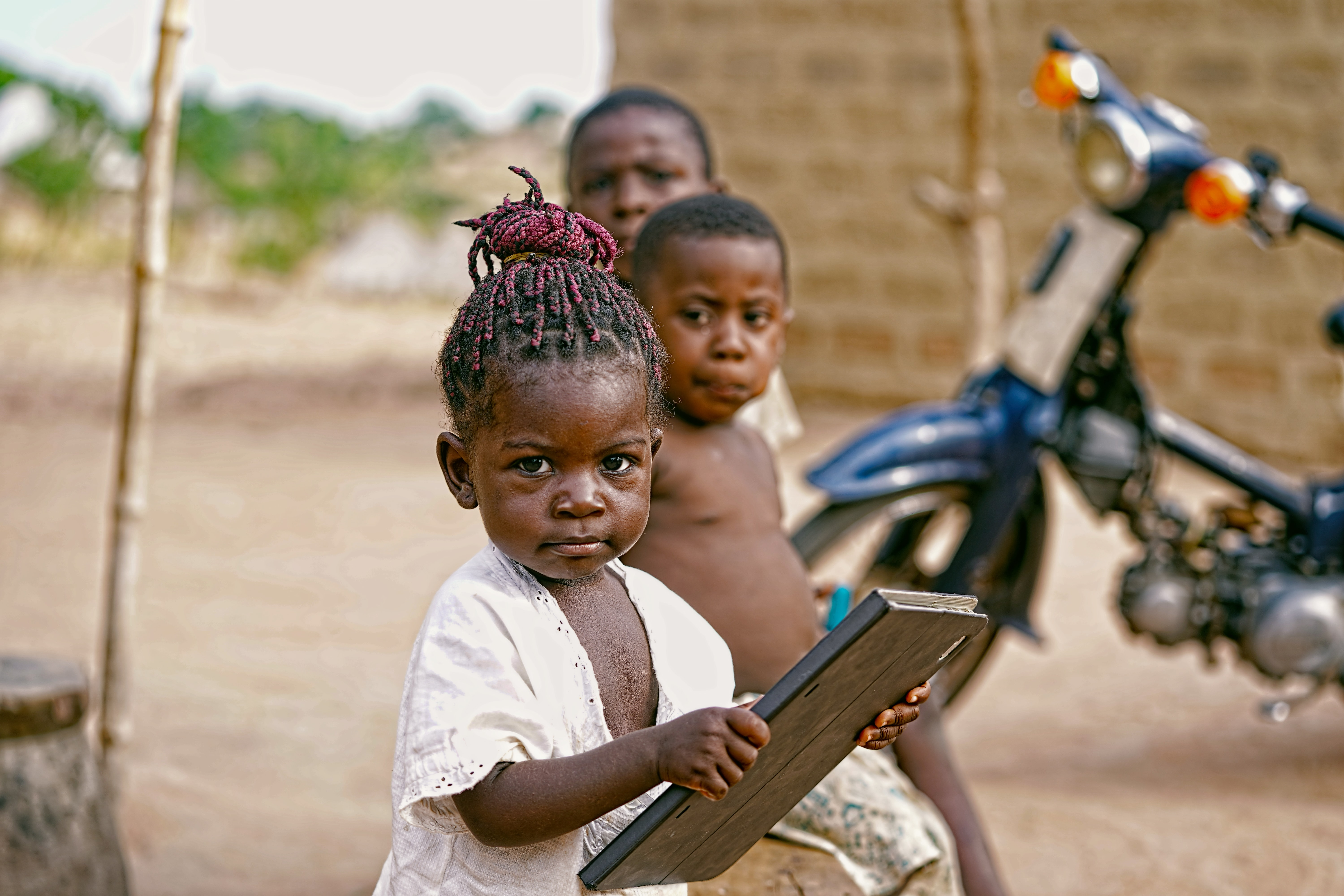 girl holding book near blue motorcycle