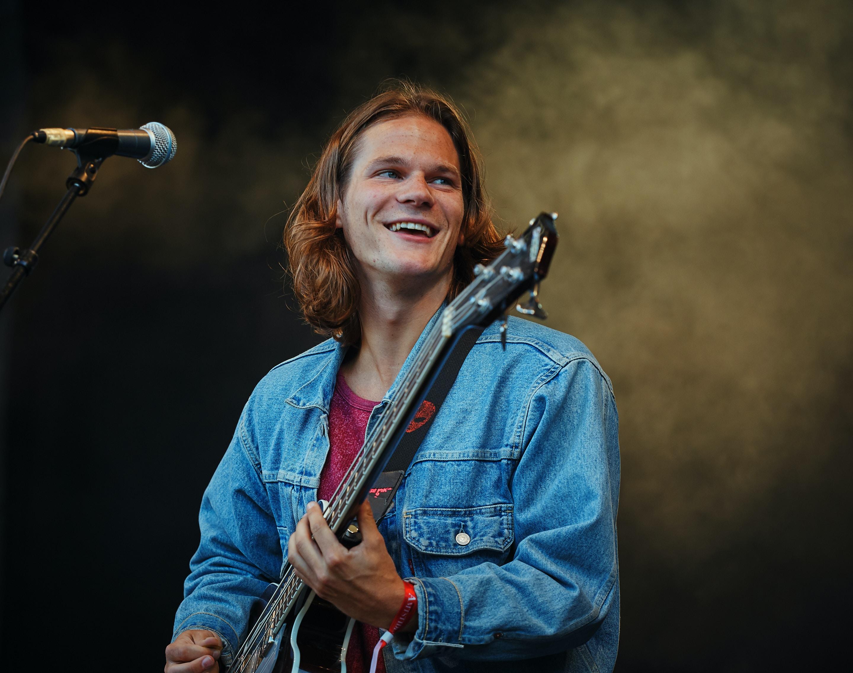 man playing guitar while looking sideway
