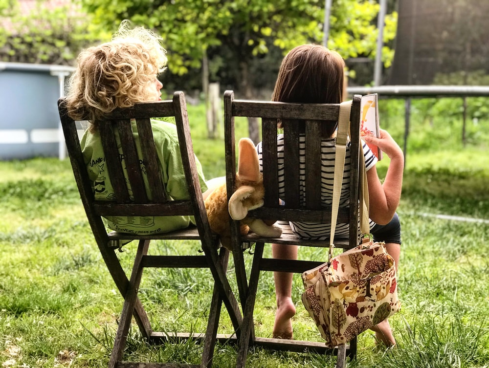 two children sitting on chairs