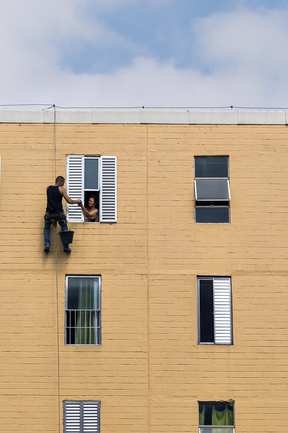 man hanging on building near woman in window during daytime