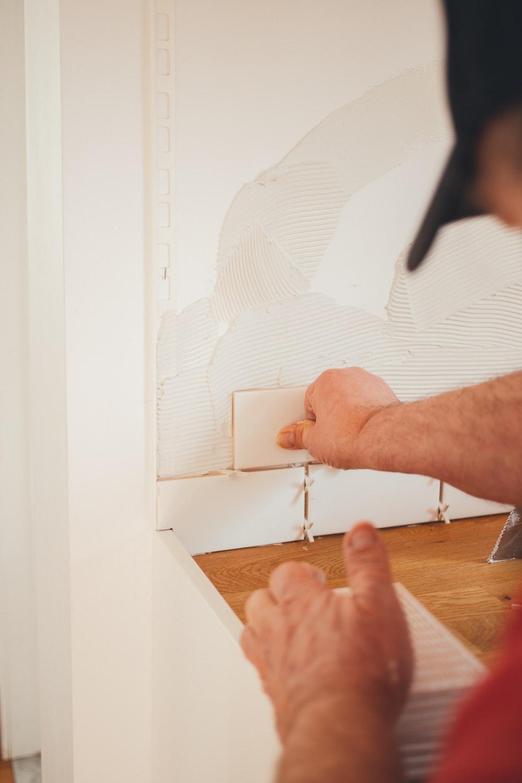 person pressing white wall