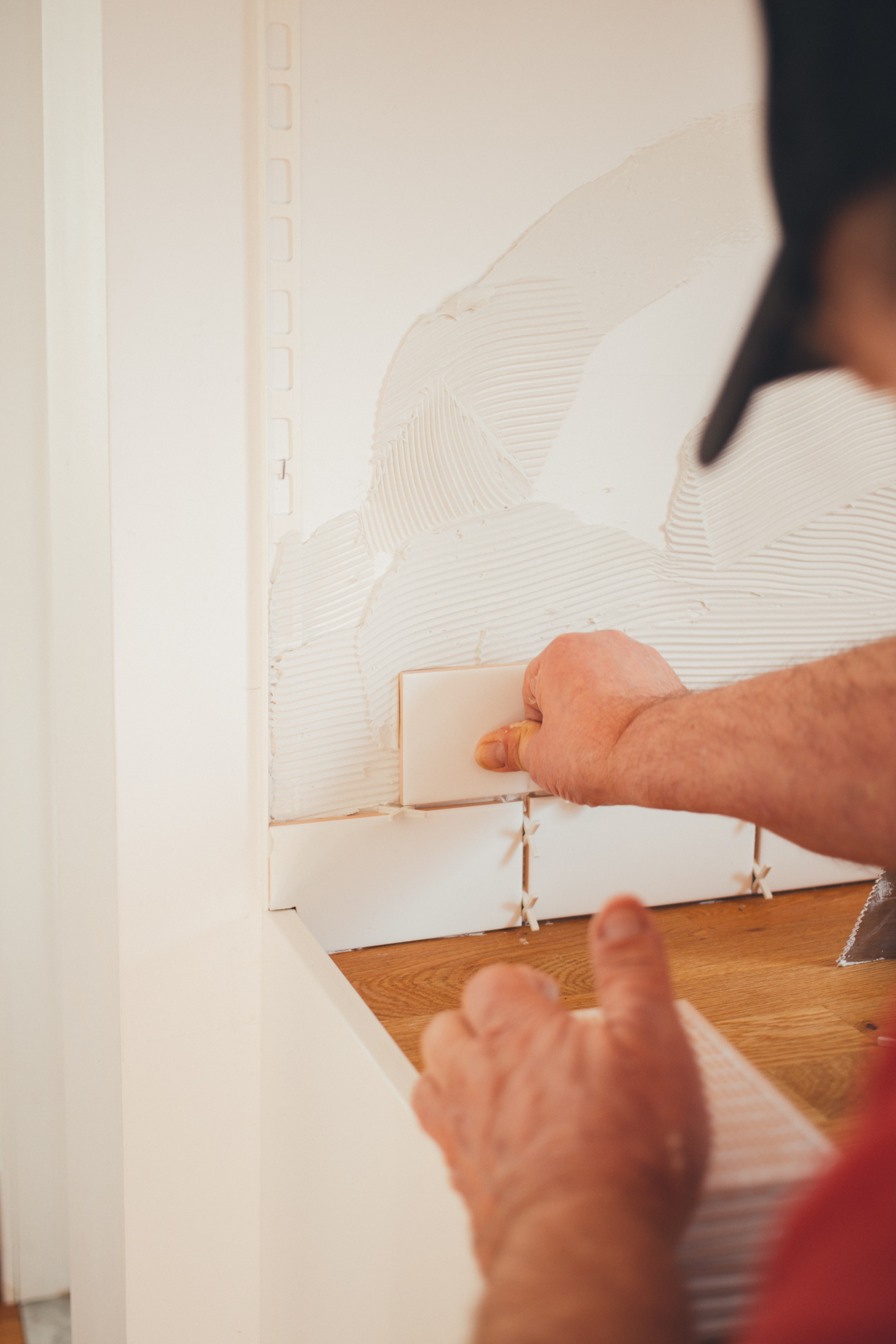 person pressing white wall