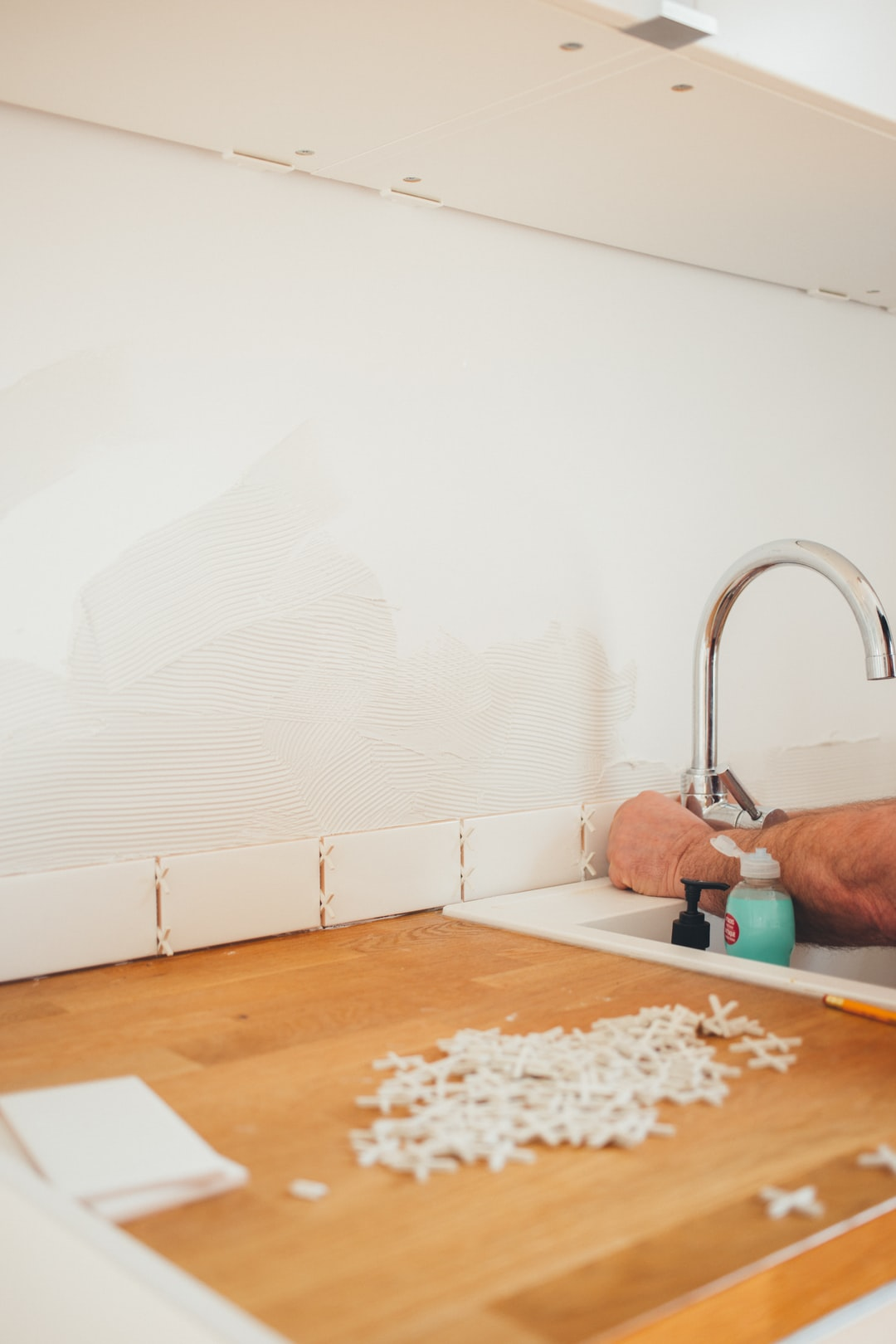 Michel the handyman is installing the kitchen tiles.