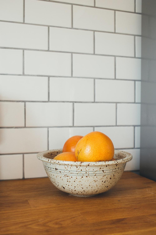 three orange fruit in white ceramic bowls on table