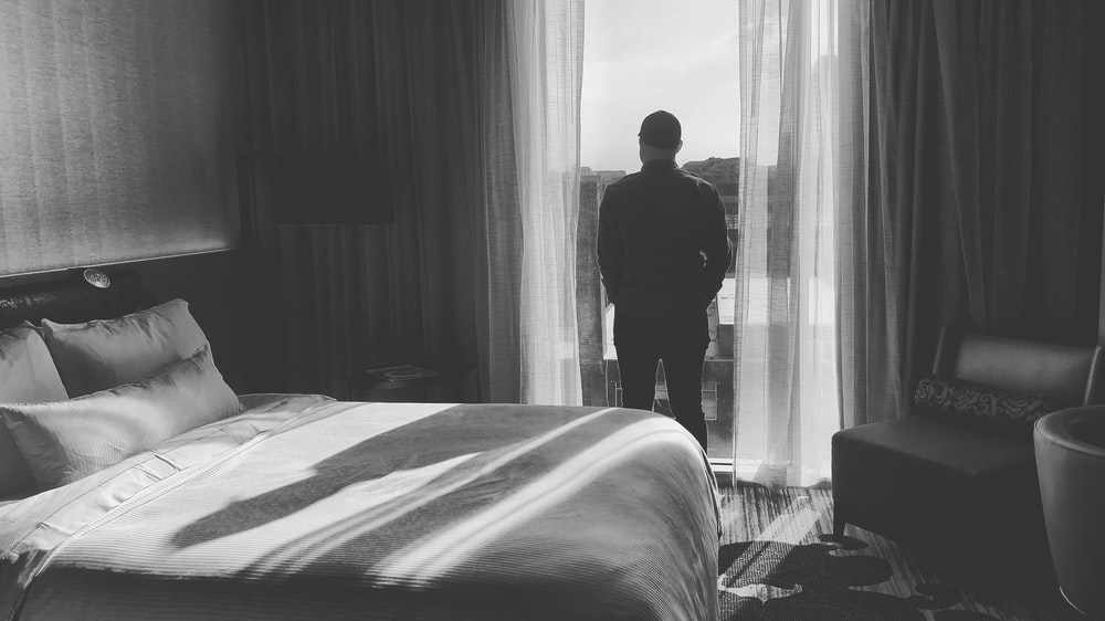 man standing in front of curtain near bed inside room