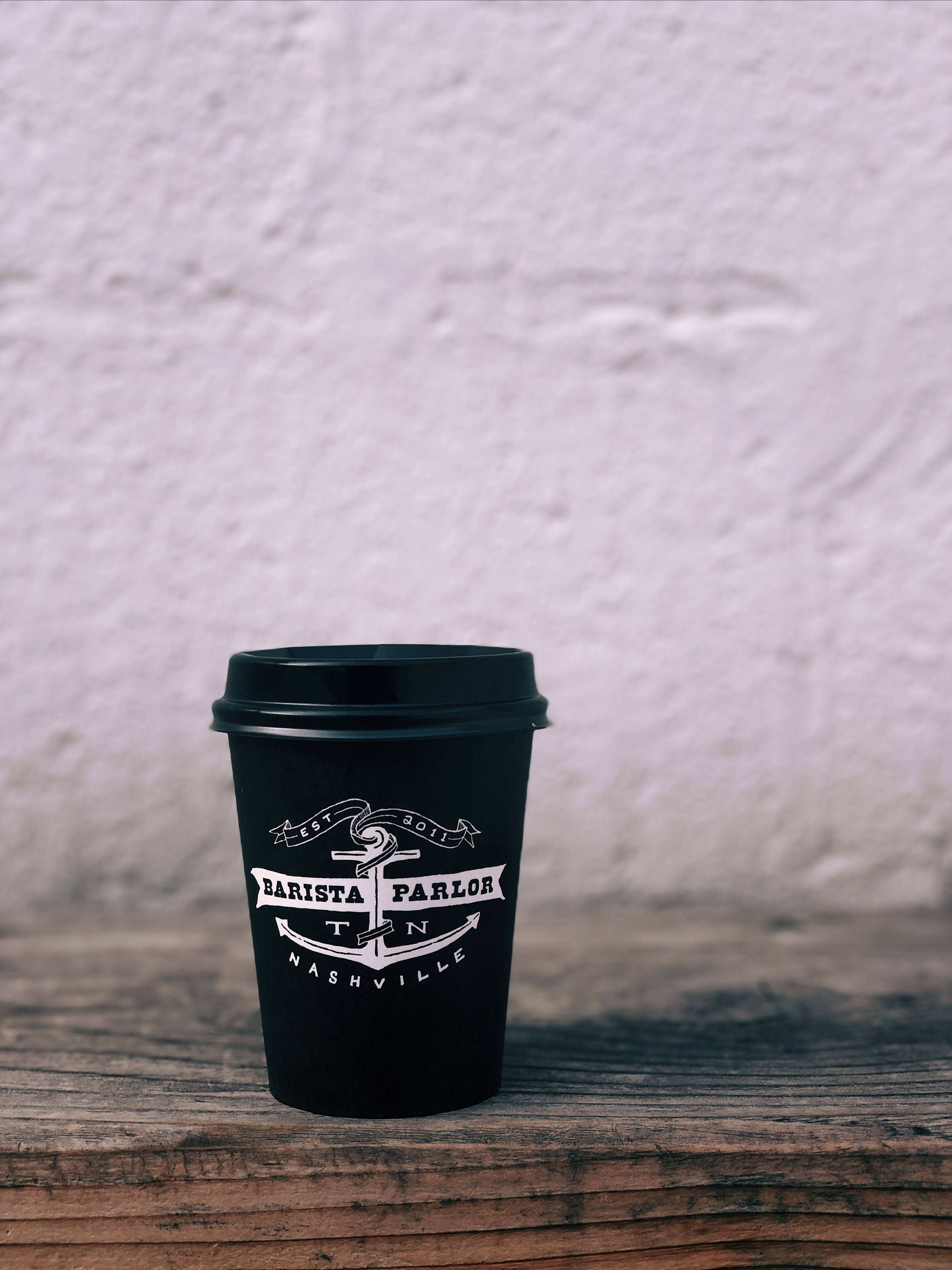 black and white Barista Parlor disposable cup on table