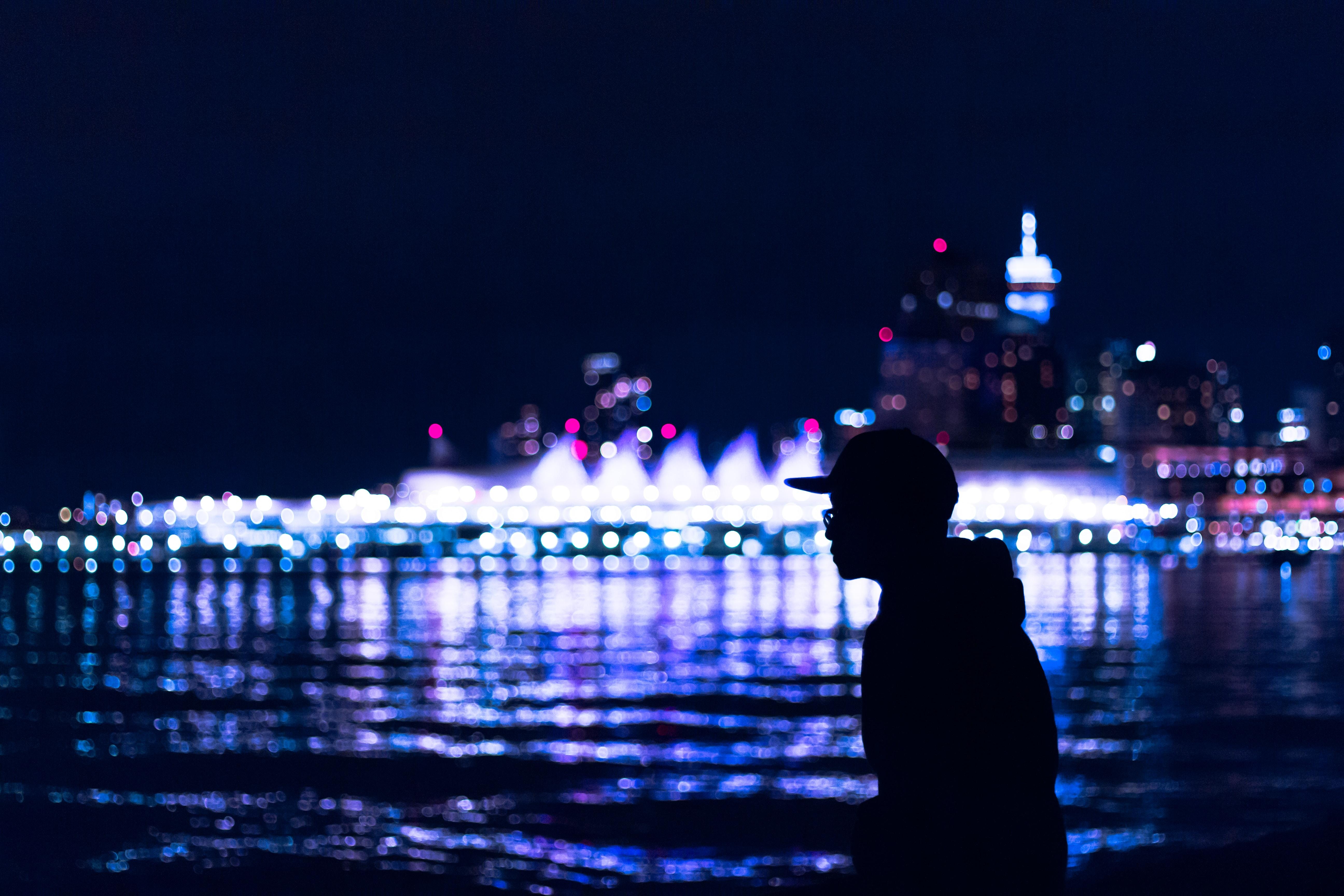silhouette of man wearing hat standing near body of water