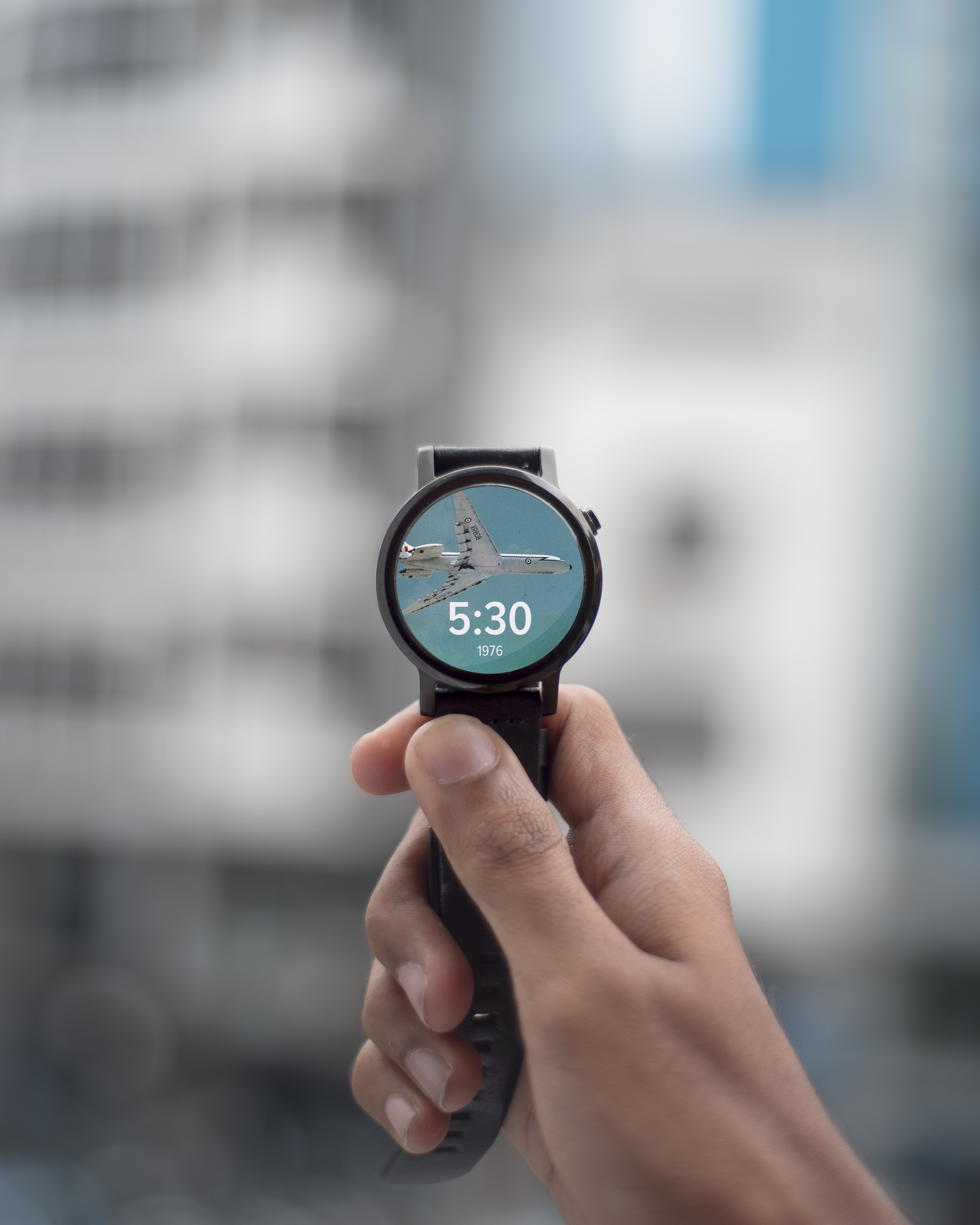 selective focus photography of person holding black smartwatch displaying 5:30