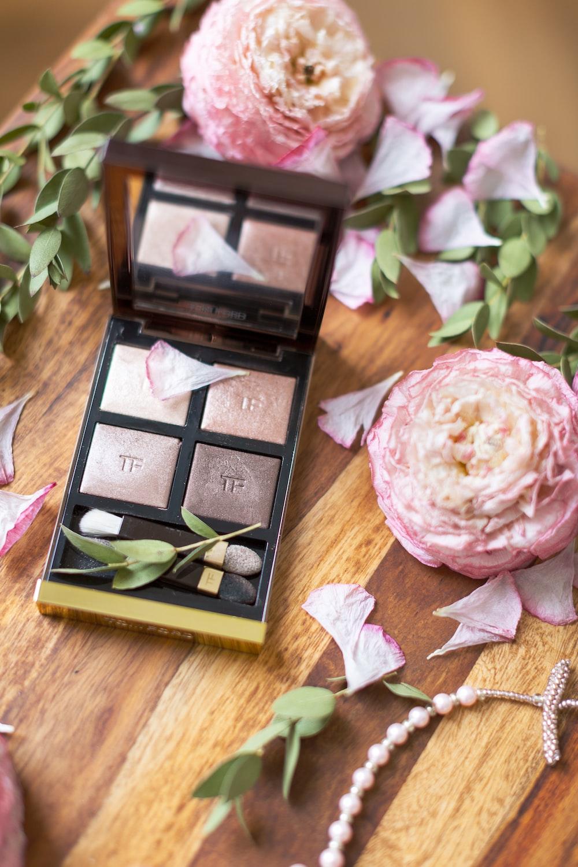 makeup palette beside pink flowers