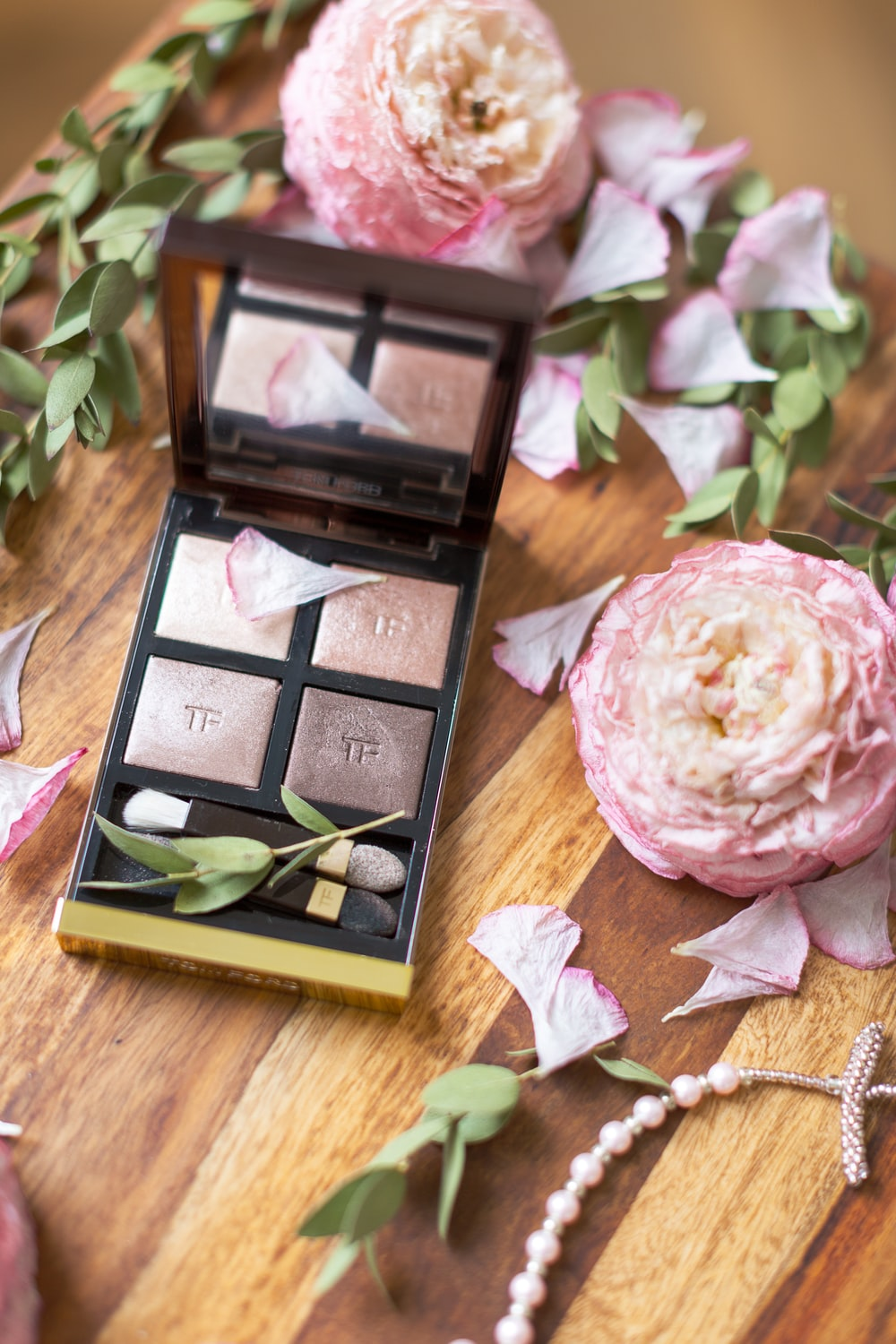 makeup palette beside pink flowers