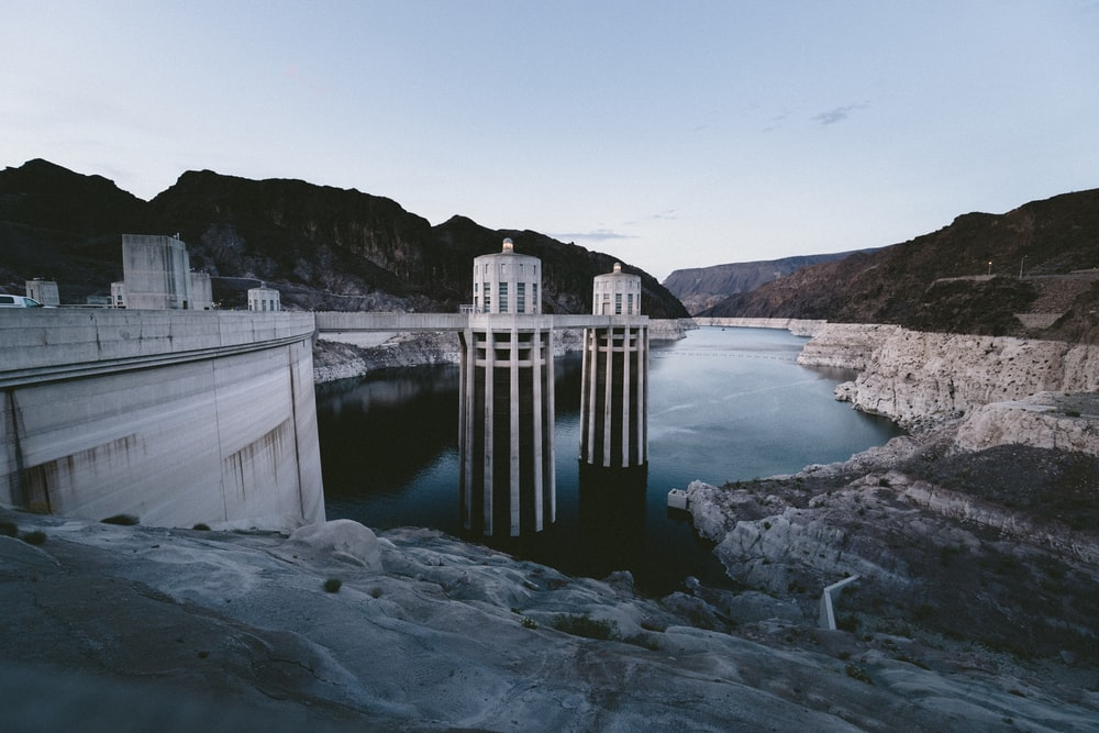 white concrete dam surrounded by mountain
