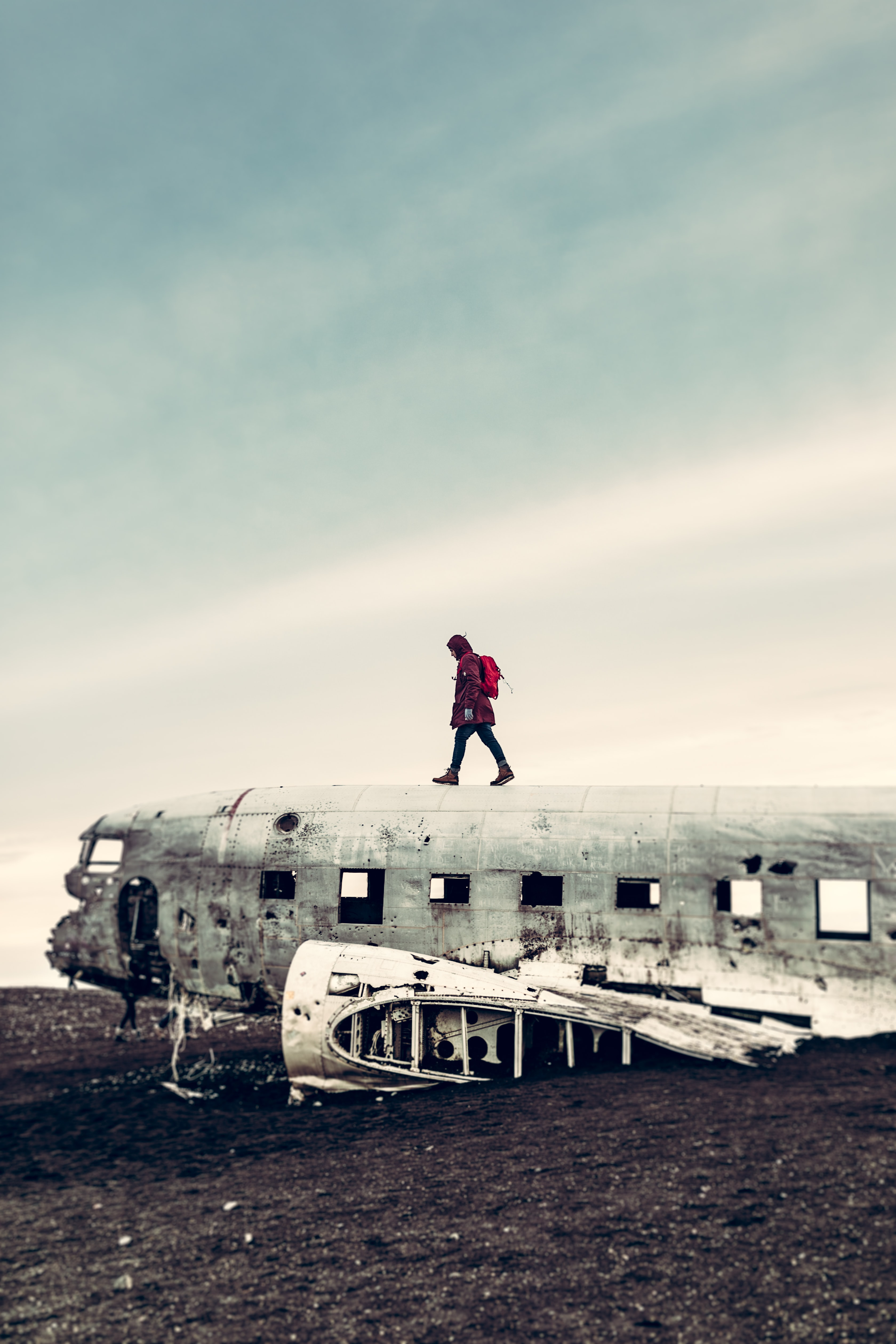 photo of person walking above wrecked plane