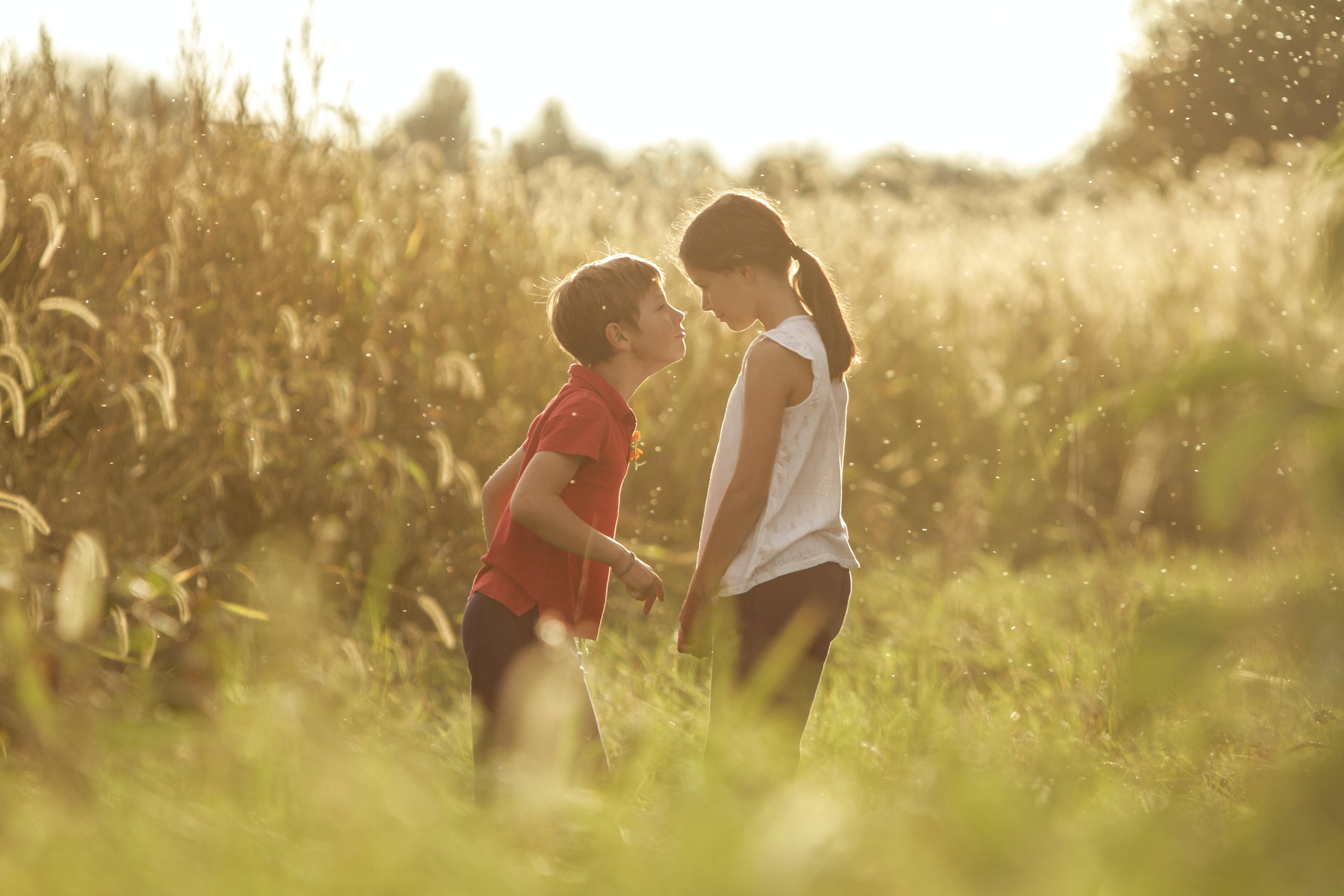 girl in white dress beside boy in red shirt standing on green grass field