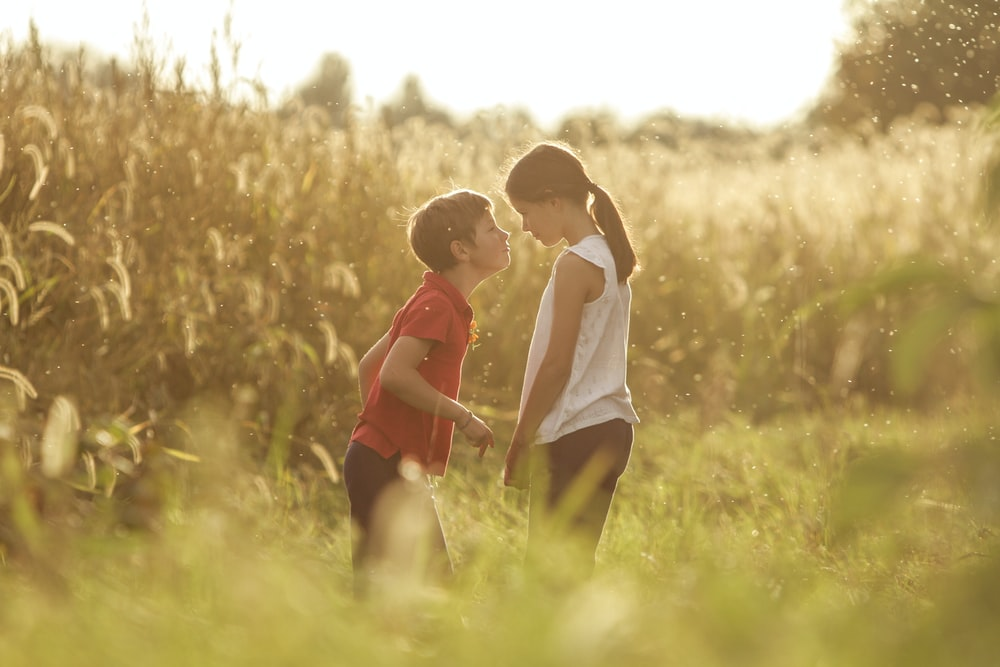 girl in white dress beside boy in red shirt standing on green grass field