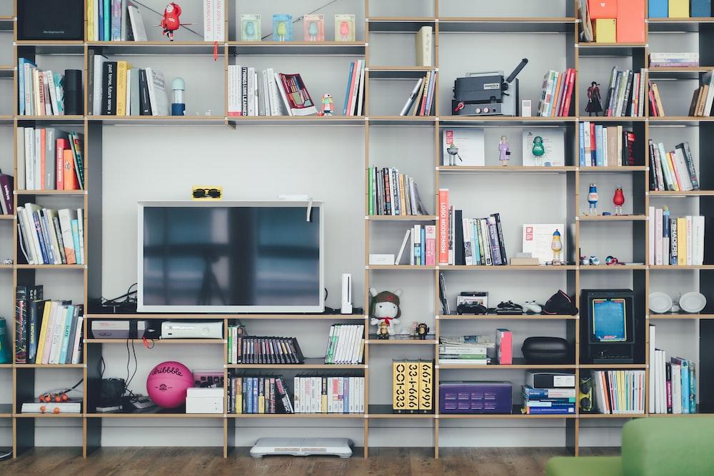 flat screen TV on brown wooden shelf