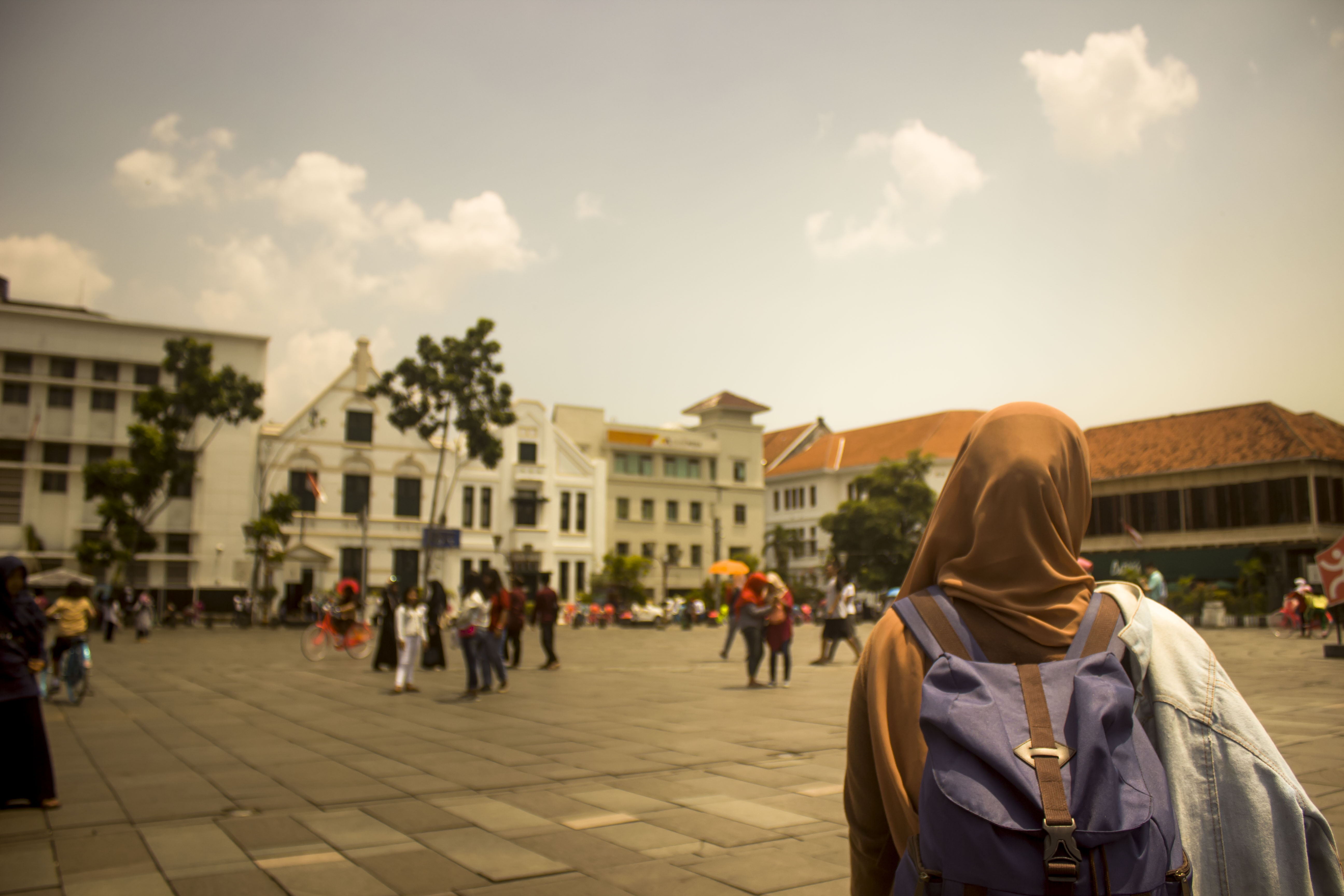 selective focus photograph of woman wearing hijab and purple backpack