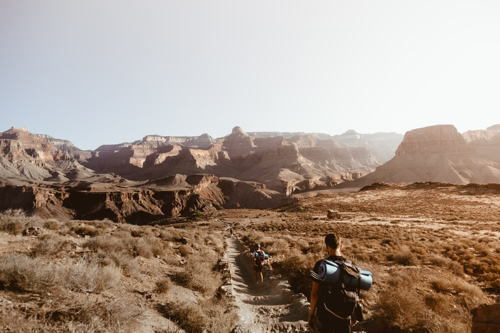 man walking on empty place surrounded by brown rock formation