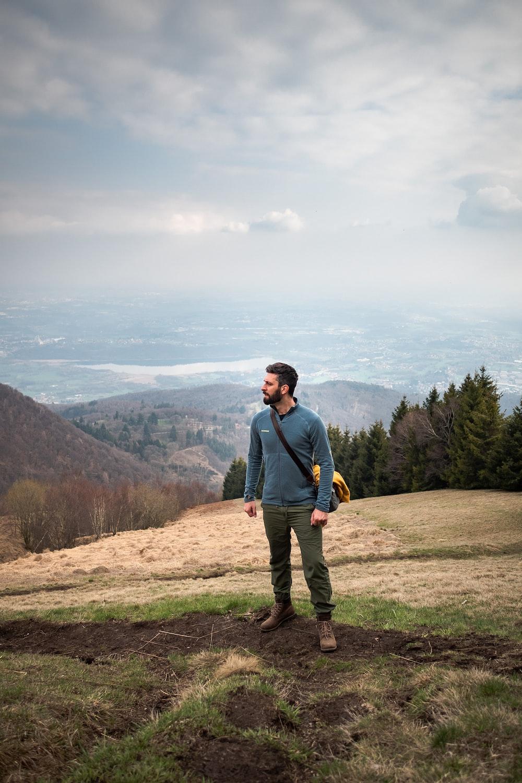 man walking on mountain carrying bag