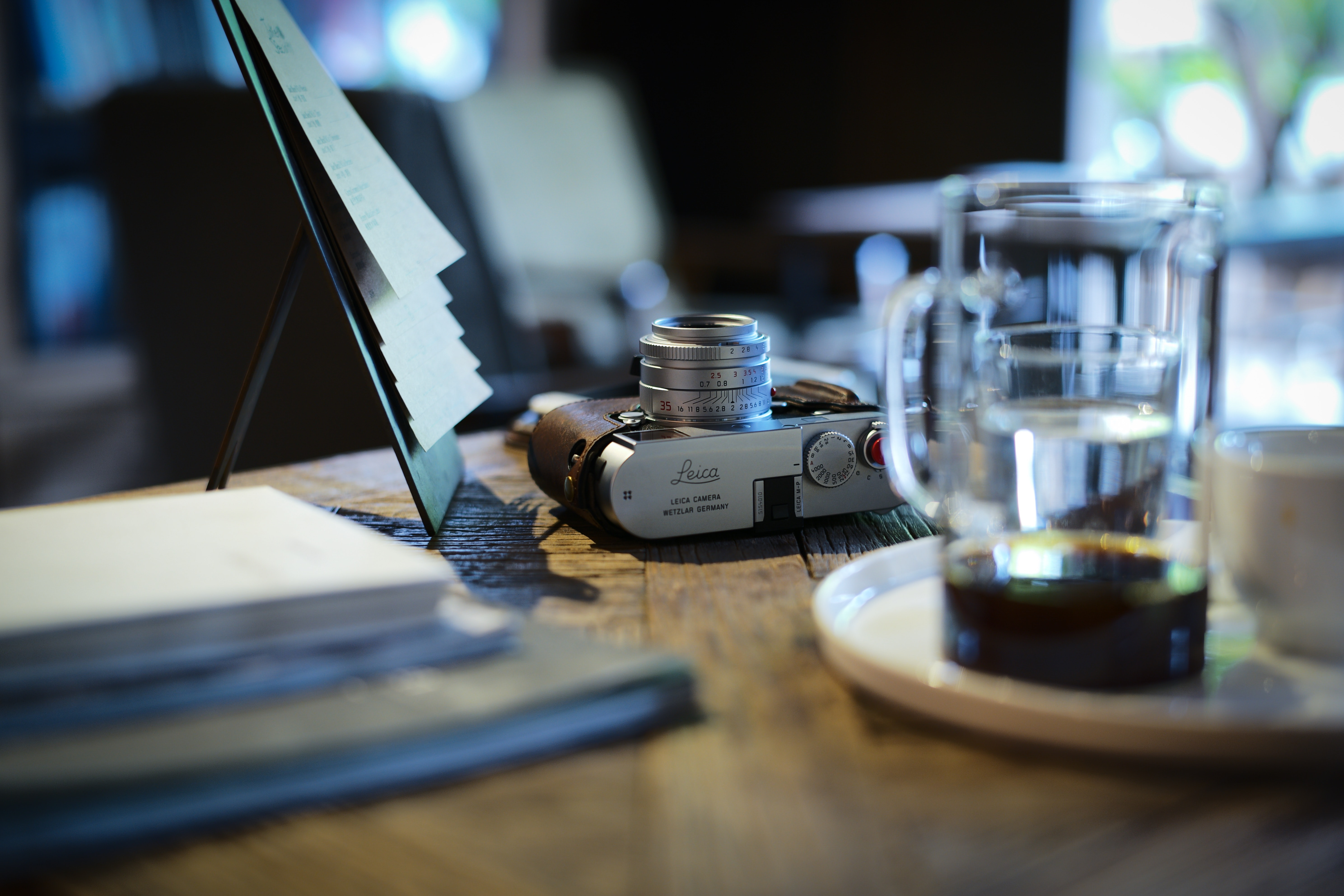 gray camera beside clear glass mug on top of table