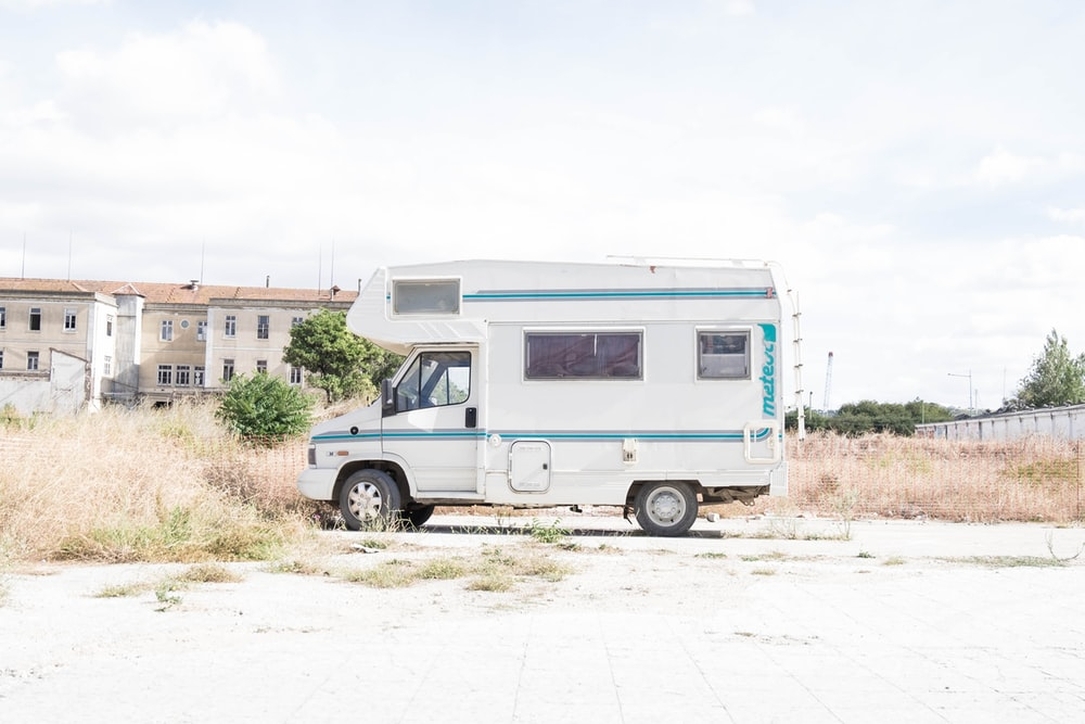 white and blue recreational vehicle parked near grass