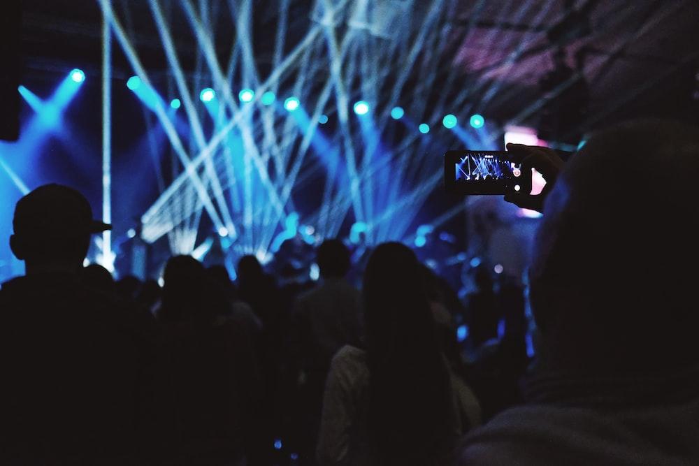 man taking video of concert inside building