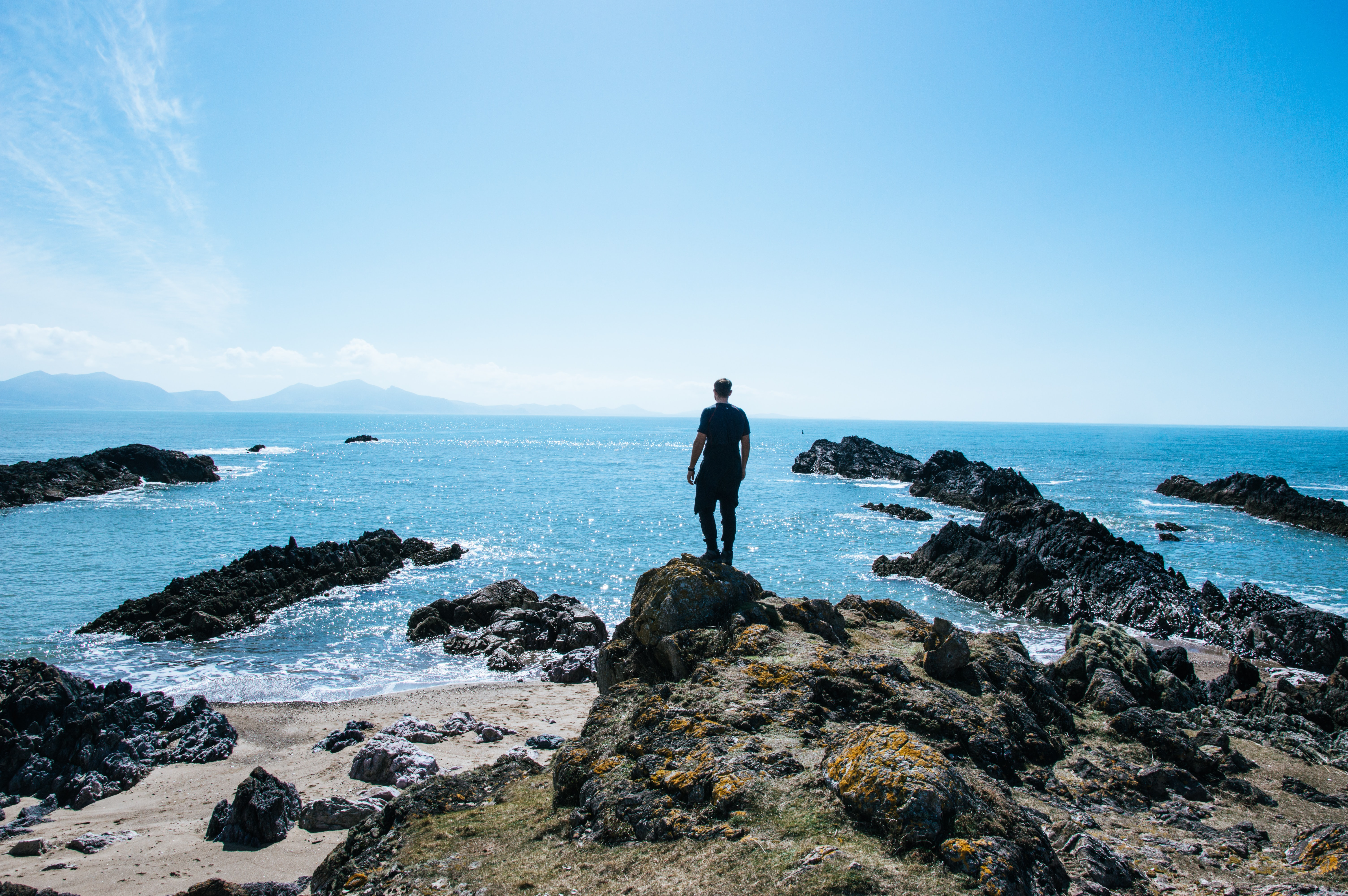 man standing on top of rock formation near body of water