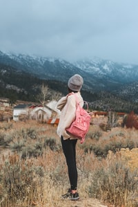 woman with pink backpack standing near grass overlooking mountains