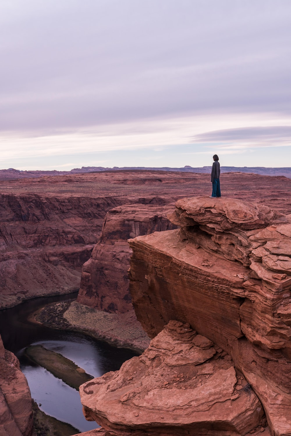 woman standing on cliff under cloudy sky