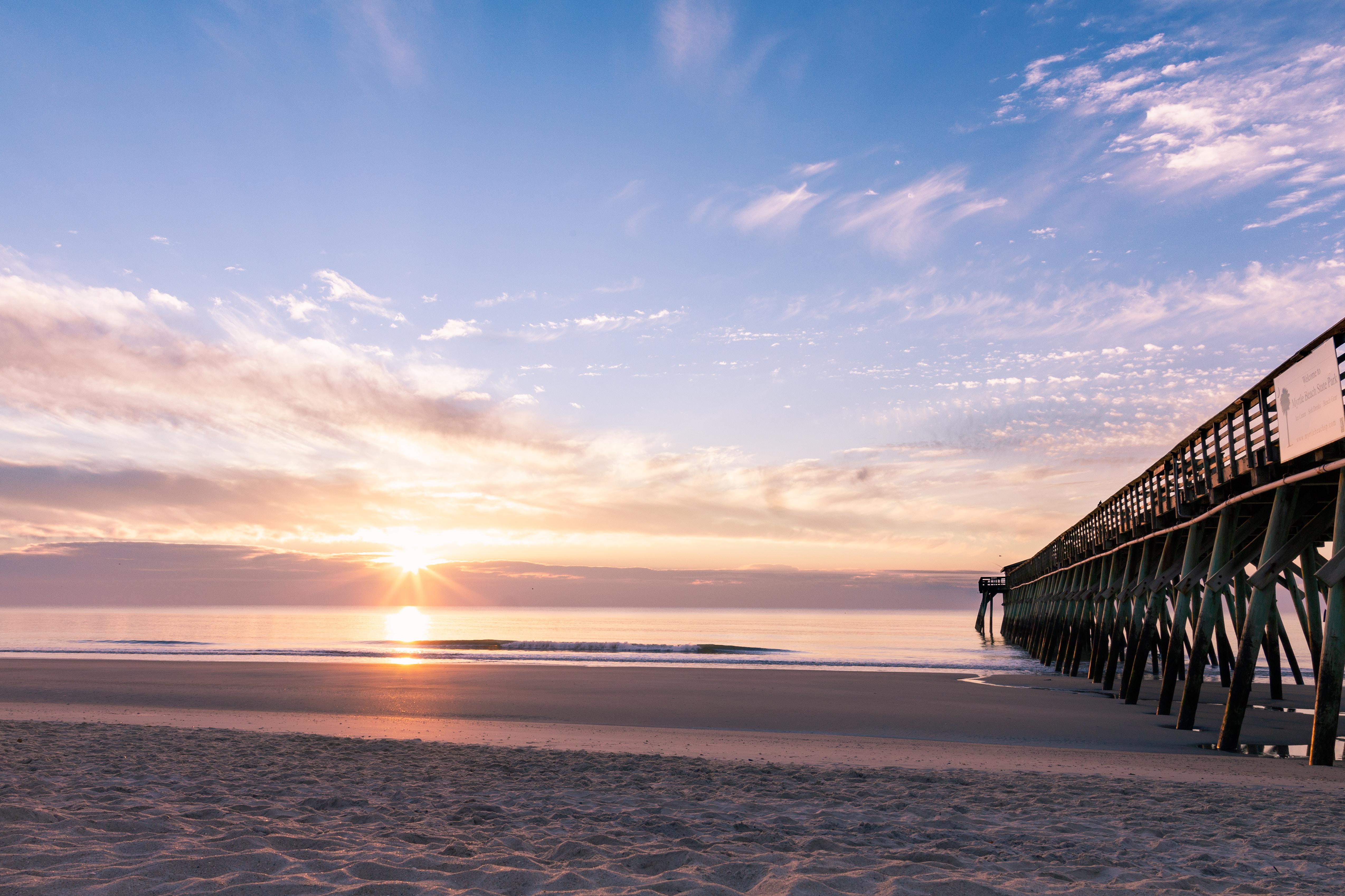 silhouette photography of black wooden dock near shoreline during sunrise