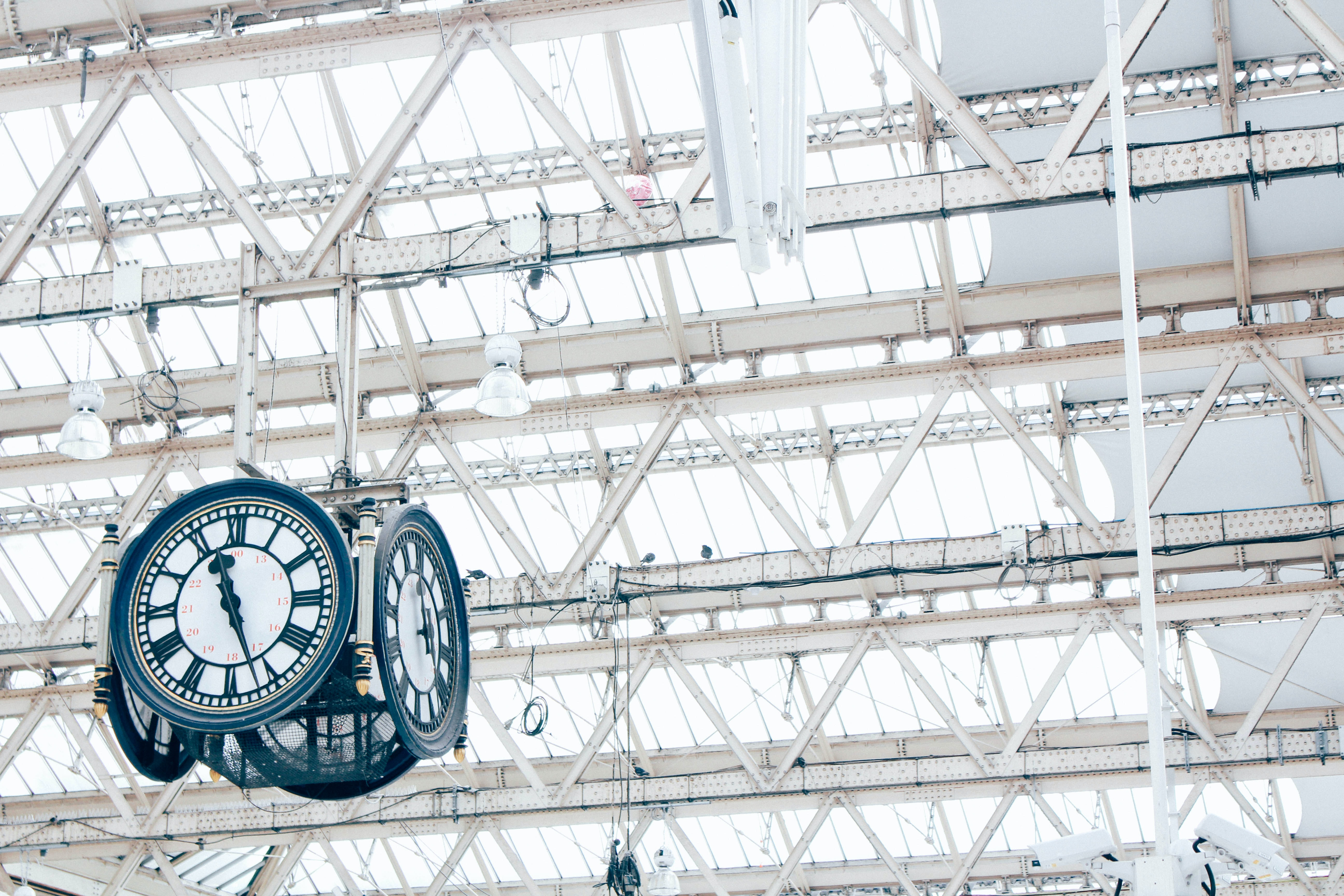 round white and blue analog hanging clock under white trusses