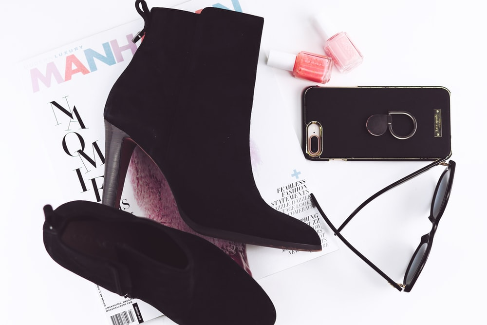 pair of black booties and iPhone 8 Plus