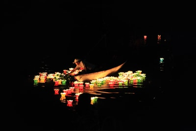 man riding on boat with lights lantern festival teams background