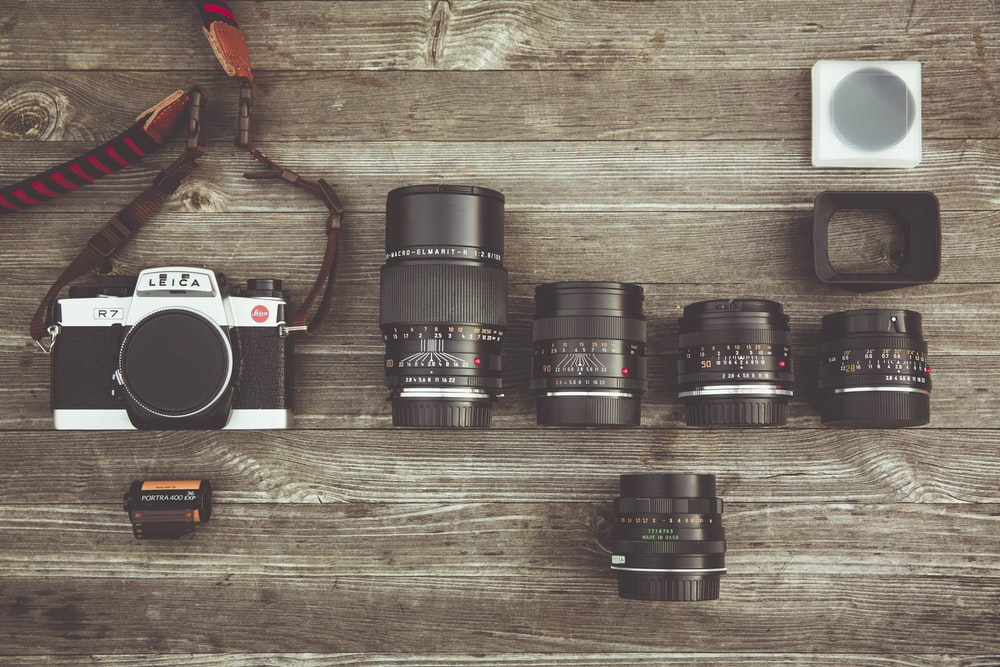 black and gray DSLR camera and lens on table