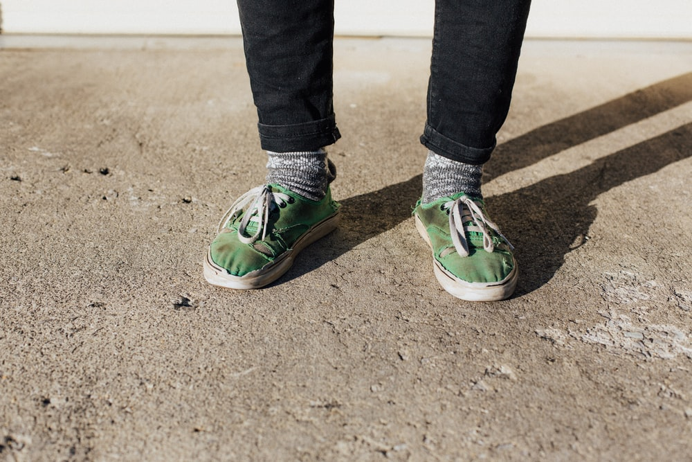 person wearing green low-top sneakers while standing