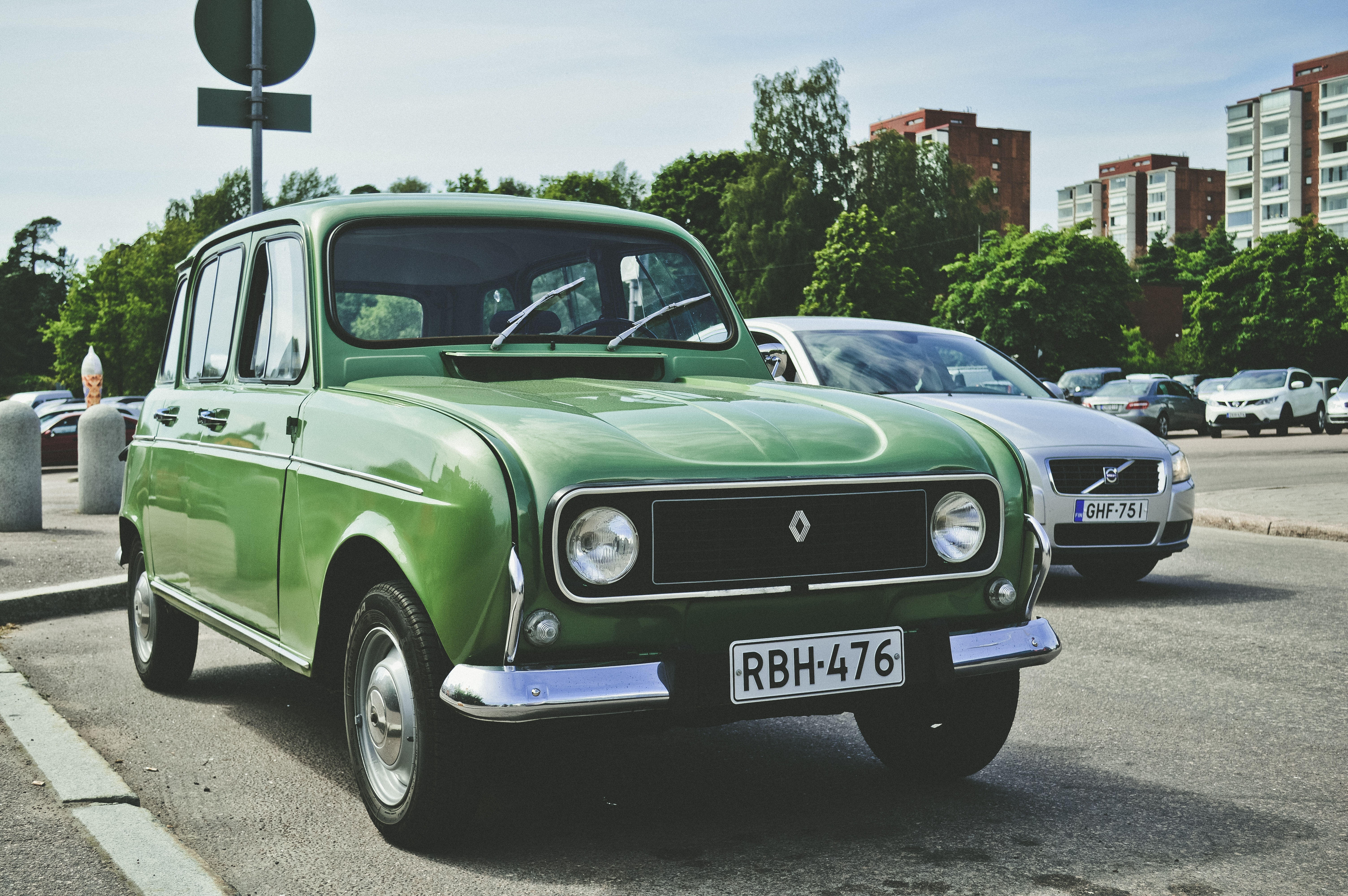photo of green Renault car parking in roadway