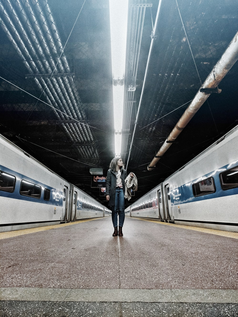 woman standing in the middle of gray trains inside train station