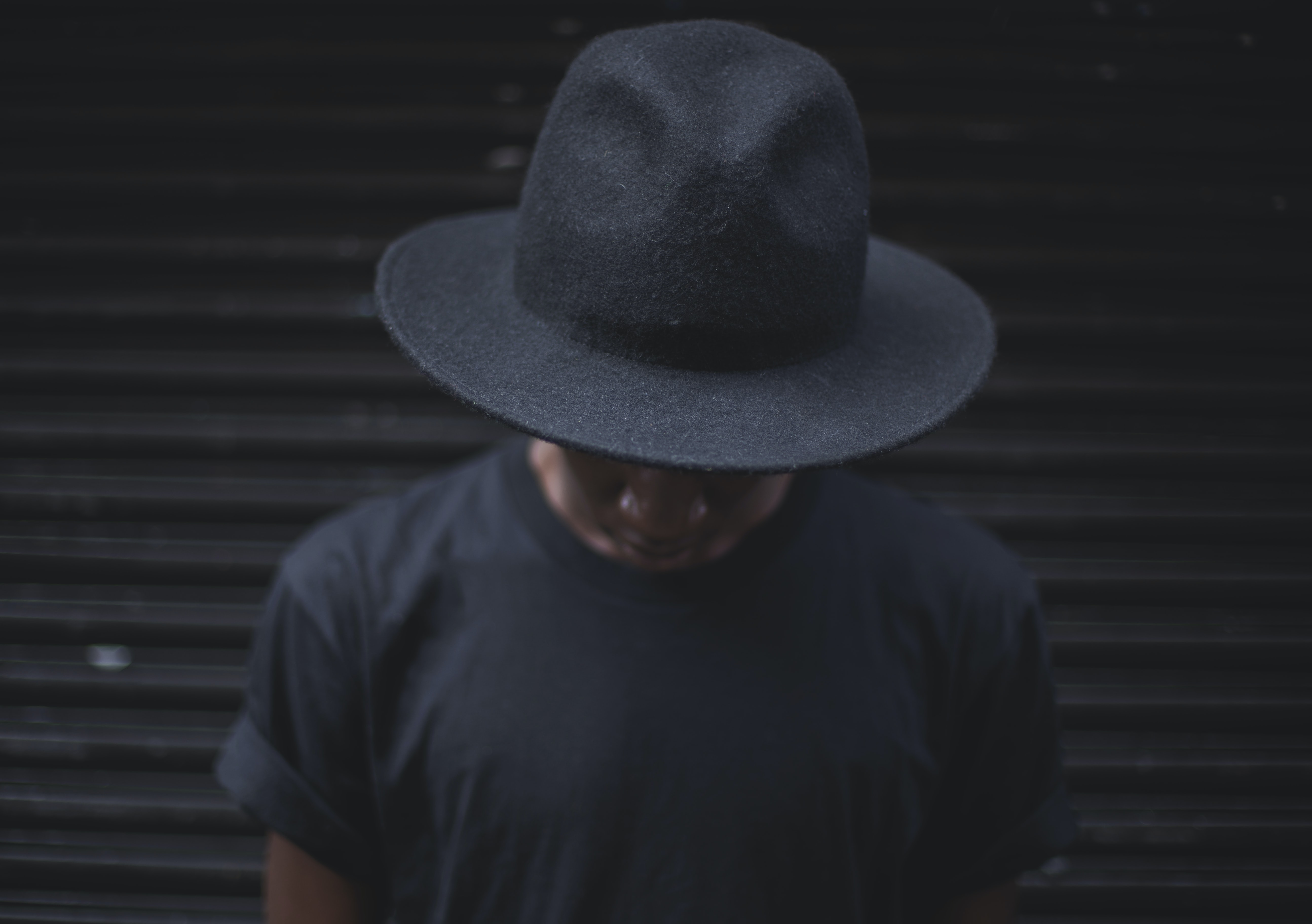 photo of person wearing black fedora hat