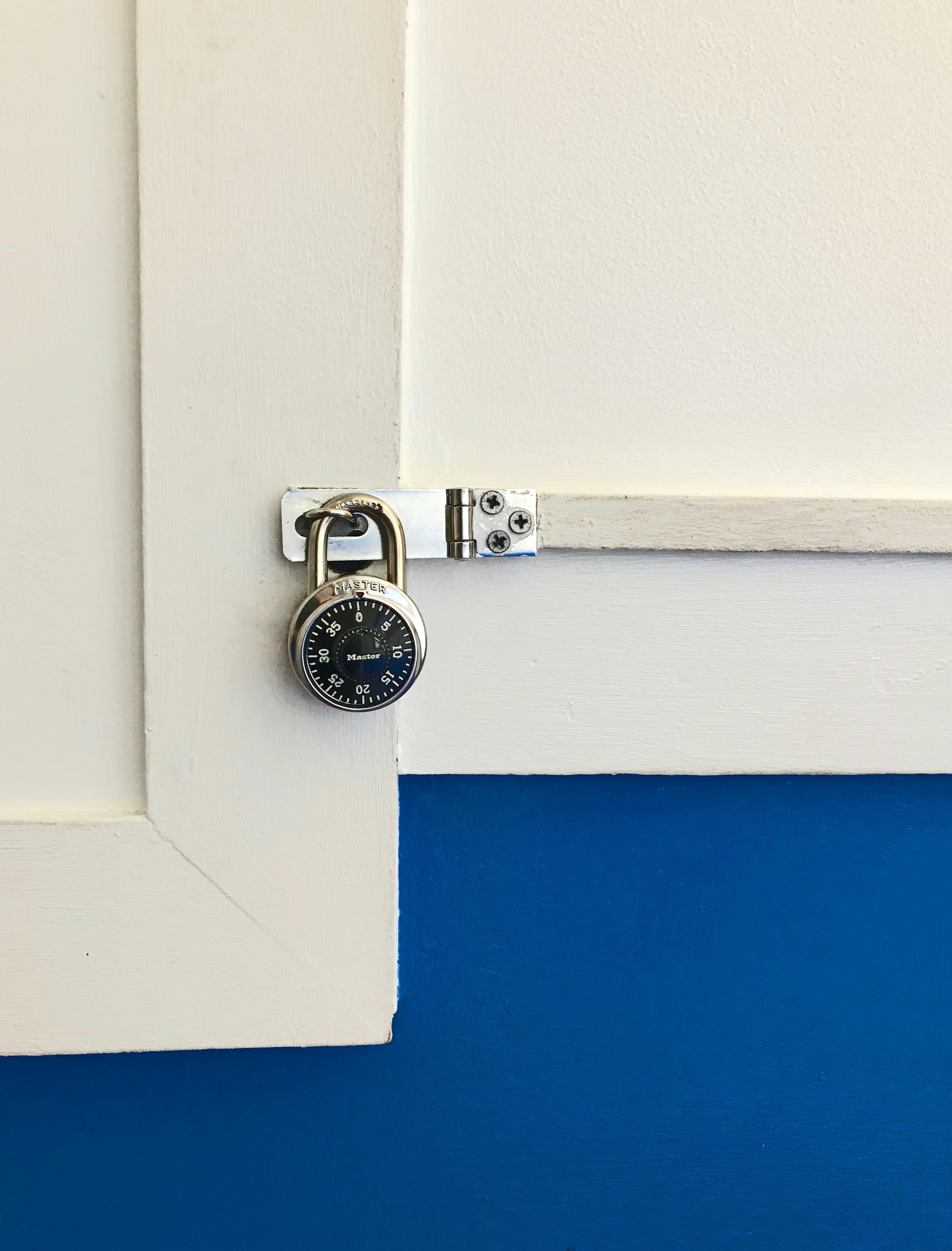 closeup photo of round gray combination padlock