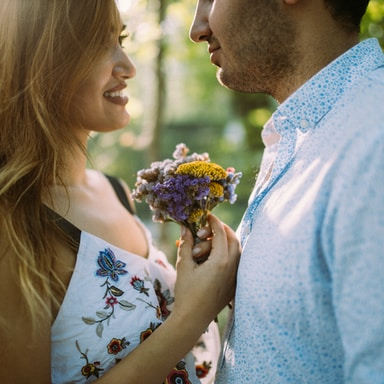 man and woman facing each other while holding flowers