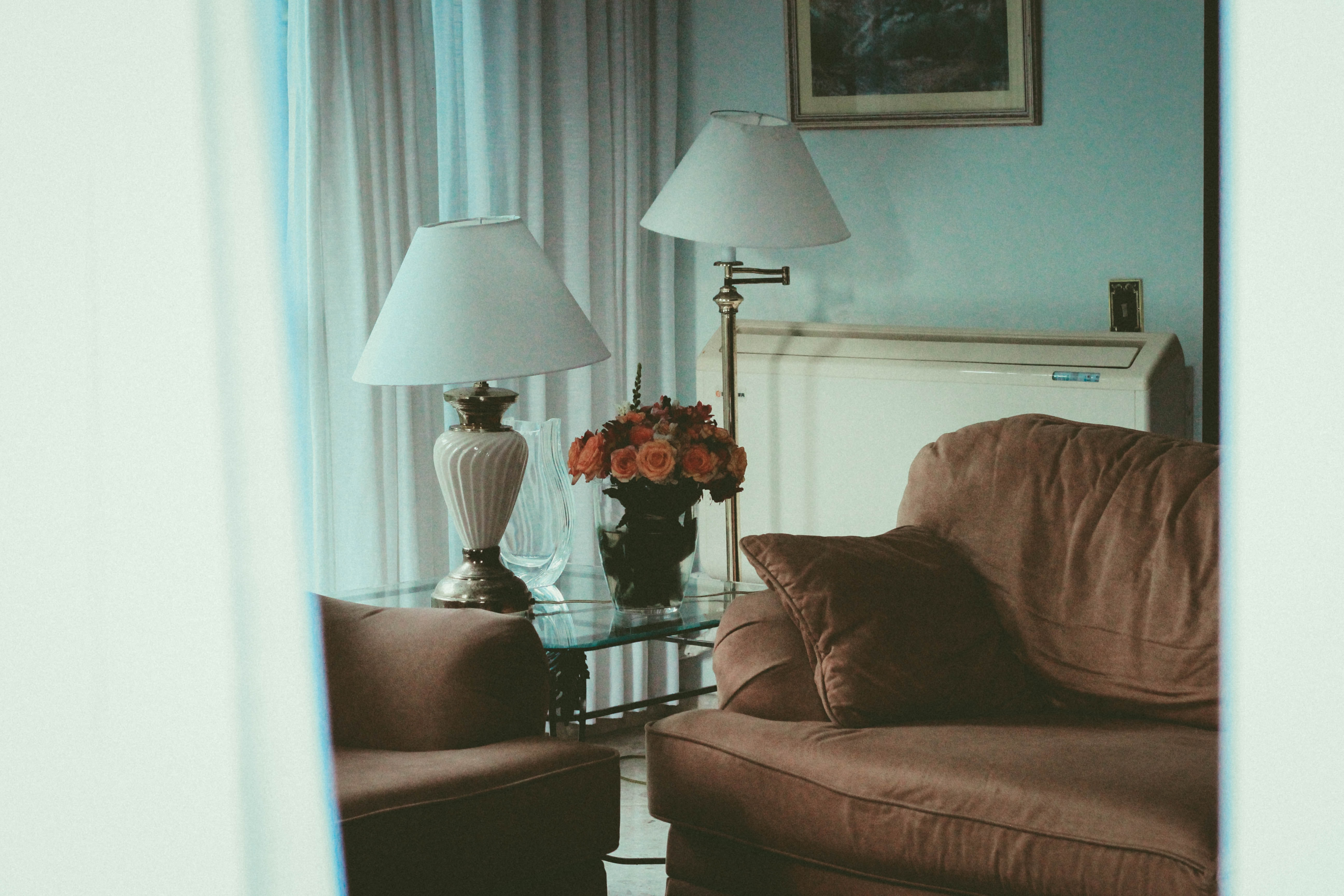 brown fabric sofa near two white table lamp and floor lamp turned off