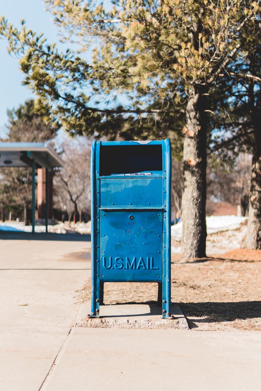 blue U.S. mail box on concrete pavement